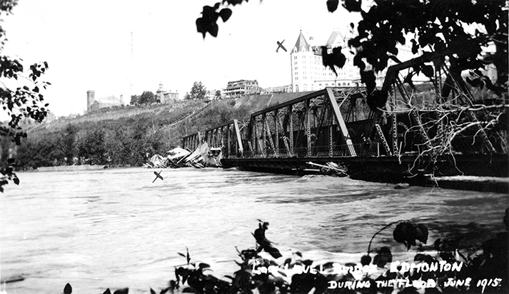 The Low Level Bridge during the flood of the North Saskatchewan River. There is debris against the bridge and the waters reach the bottom of the bridge. The Hotel Macdonald, Edmonton Club, College Avenue School and McDougall Church can be seen in the background. Image courtesy of the City of Edmonton Archives EA-10-238.