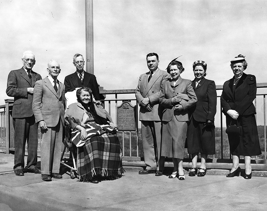 "The Latta Bridge Grand Opening May 28, 1952 with Mr. Roxborough, W. Everard Evans, A. A. Campbell, Mrs. T. H. Field (seated), Emily Latta (front), William Hawrelack, Mrs. A Teviotdale, Mrs. M. Williams. Plaque reads ""City of Edmonton Archives & Landmarks Committee Latta Bridge named in Honor of David Gilliland Latta, Pioneer Edmonton Businessman 1897-1948, Alderman 2nd Council 1908."" Image courtesy of the City of Edmonton Archives EA-10-309."